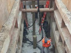 A work crew installing piles to support new sewer and drain pipes