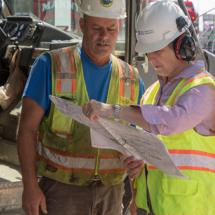 Two construction workers examining the site plan